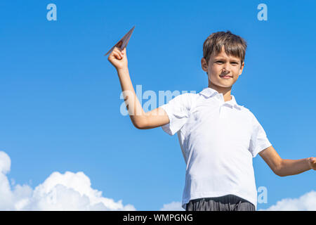 Happy kid playing with paper airplane against blue summer sky background - Stock Photo