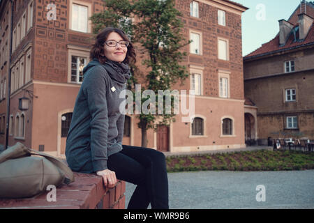 Outdoor portrait of young beautiful lady posing on old street. Evening old Warsaw, Poland, spring - Stock Photo