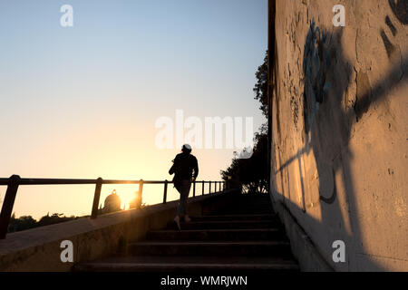 Silhouette Woman Walking On Steps Against Sky During Sunset - Stock Photo