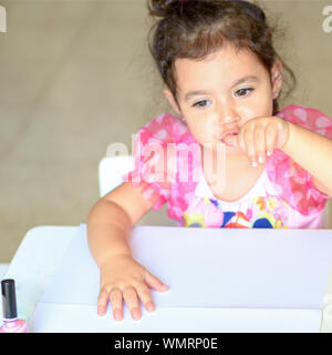 Adorable little girl having fun playing at home with colorful pink nail polish doing manicure and blowing nails. Toddler cute child in pink elegant dress sitting wood white table and making manicure - Stock Photo