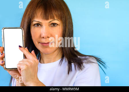 Closeup of woman using smartphone. She smile touching on the screen with a finger. Mock up mobile phone white color blank screen - Stock Photo
