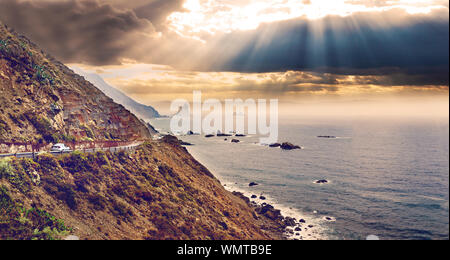 Seascape of sunset and road on the cliffs of the island of Tenerife. - Stock Photo