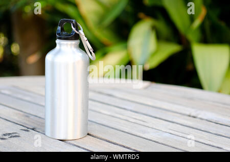 Reusable water bottle on a wooden table outdoors - Stock Photo