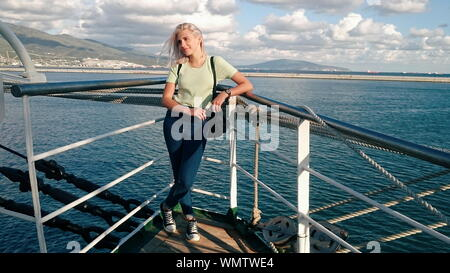 Young Woman Leaning On Railing Of Ship In Sea Against Sky - Stock Photo