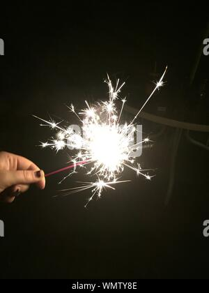 Close-up Of Woman Hand Holding Sparkler At Night - Stock Photo