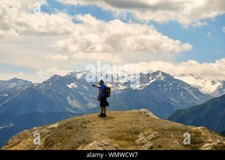 Elevated mountain view with a hiker taking pictures with smartphone from a rock of the Mont Blanc massif in summer, Courmayeur, Aosta Valley, Italy - Stock Photo