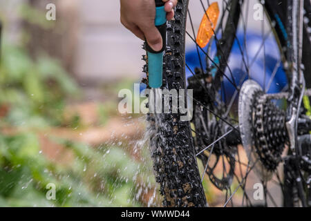Child repairs and cleans his bike with water - Stock Photo