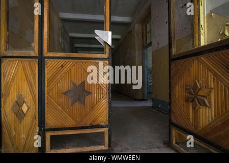 Interior with wooden doors at derelict Russian barracks left behind by the Soviet Red Army in 1994, decaying in Germany - Stock Photo