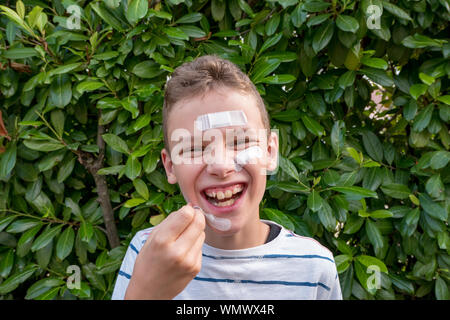 Boy with plaster on his face in front of a hedge laughing - Stock Photo