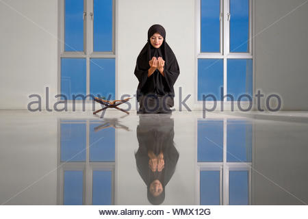 Muslim women wearing hijab ask for dua or pray to God during the holy month of Ramadan at the mosque - Stock Photo