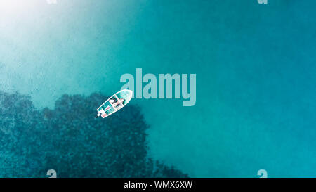 aerial drone view from the top to the blue lagoon with azure sea water with a boat with copy space, vacation travel concept - Stock Photo
