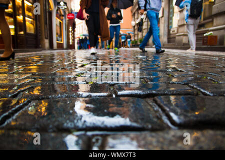 Low Section Of People Walking On Wet Street During Monsoon - Stock Photo