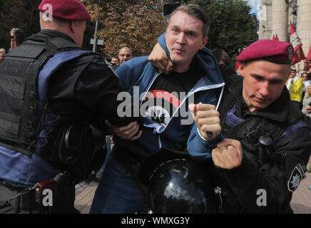 September 5, 2019: Police detains an activist during the protest in front of the National Council of Television and Radio Broadcasting of Ukraine in Kyiv, Ukraine, 05 September 2019. Protesters demand to stop licenses of the News One and 112 Ukrainian TV Channels because they provide anti-Ukrainian politics and are the tool of information expansion of Russia in Ukraine as activists told. Protestors hold placards reading like 'Putin + his supporters = News One', 'No to information attack of the Russia', 'May be enough?' and so on. (Credit Image: © Sergii Kharchenko/ZUMA Wire) - Stock Photo
