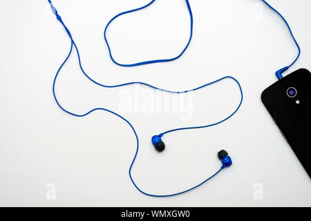 Close-up Of Mobile Phone With In-ear Headphones On White Background - Stock Photo