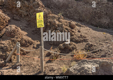 NAPLES, ITALY - AUGUST 2019: Warning sign on side of the path around the crater of Mount Vesuvius on the outskirts of Naples. - Stock Photo
