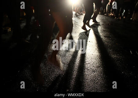 Low Section Of People Jumping On Road During Protest On Street At Night - Stock Photo