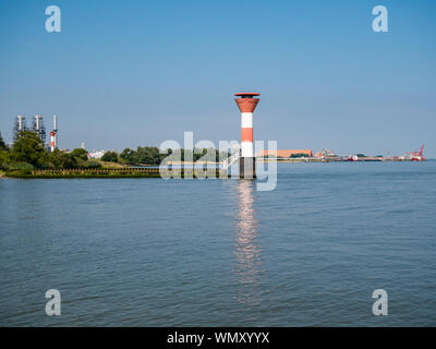Stadersand, Germany - August 25, 2019: View from jetty Stadersand at lighthouse and Radar station. DOW Chemical and BUSS Terminal at small town of Bue - Stock Photo