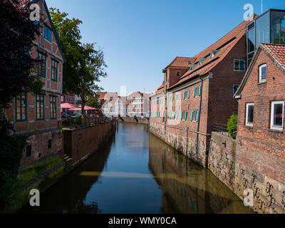 Stade, Germany - August 25, 2019: View at Schwinge River and old historical town of Stade.  Museum named Schwedenspeicher at the right. - Stock Photo