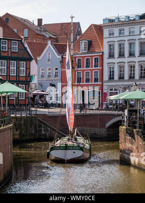 Stade, Germany - August 25, 2019: View at Schwinge River and historical center of Stade. Sail of old ship is used for advertising purpose. - Stock Photo