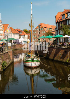 Stade, Germany - August 25, 2019: View at Schwinge River and historical center of Stade in Germany. Sail of old ship is used for advertising purpose. - Stock Photo