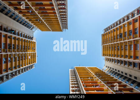 Directly Below Shot Of Residential Buildings Against Blue Sky - Stock Photo