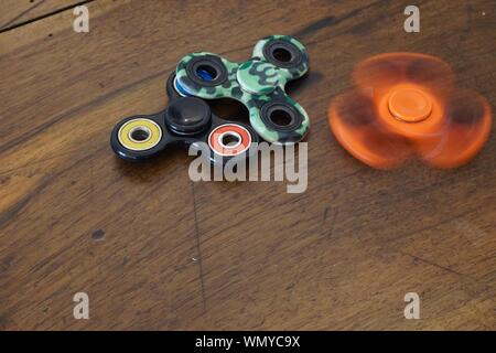 High Angle View Of Colorful Fidget Spinners On Wooden Table - Stock Photo