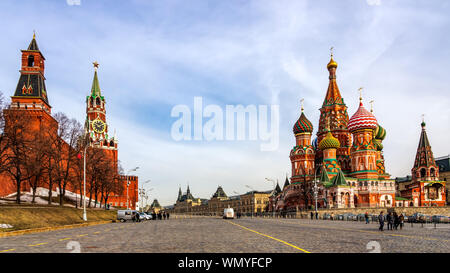 Moscow, Russia, April 2013 Tourists visiting St Basils Cathedral, Beautiful Spasskaya Tower and The Tsars Tower on the Red Square at beautiful sunrise - Stock Photo