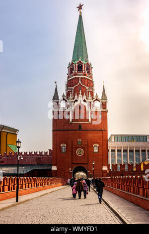 Moscow, Russia, April 2013 Tourists visiting Kremlin, passing through Troitskiy Bridge and entrance at Troitskaya Tower, beautiful sunrise - Stock Photo
