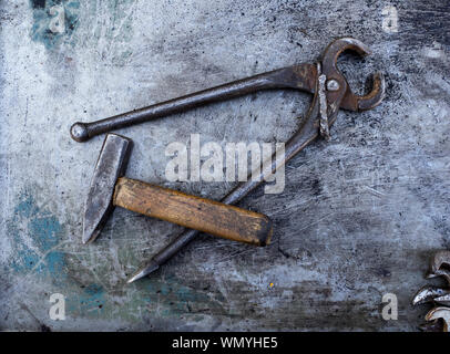 Directly Above Shot Of Rusty Pincers And Hammer On Scratched Metal Table - Stock Photo
