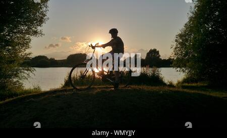 Boy With Bicycle On Road By Lake Against Sky During Sunset - Stock Photo
