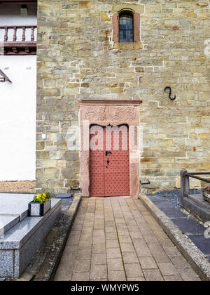 Historic Church of St. Peter in the village of Beho, Belgium, exterior partial view with beautiful old entrance door - Stock Photo