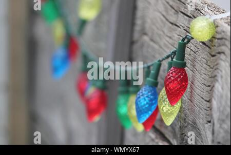 Christmas Lights Hanging On Wooden Wall - Stock Photo