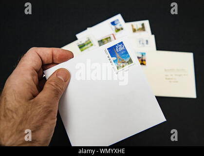Paris, France - Dec 23, 2018: Man hand holding isolated on black background letter with stamp featuring Eiffel Tower - Stock Photo