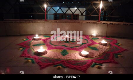 Close-up Of Diyas Burning On Rangoli In Balcony At Night - Stock Photo