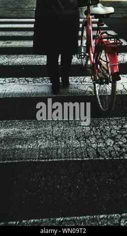 Low Section Of Woman With Red Bicycle On Crossroad - Stock Photo