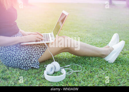 Female sitting on greed grass by relaxing and typing keyboard of laptop and ear plug putting on the ground in the park - Stock Photo