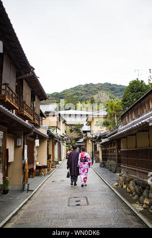 A couple dressed in the traditional Kimono are walking through the streets of Kyoto. - Stock Photo