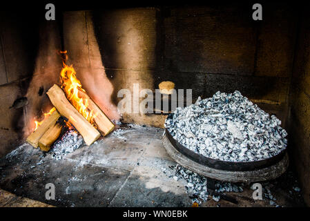 Cooking of traditional Balkan Greek Mediterranean Croatian meal Peka in metal pots called sac sach or sache or a metal lid. Fireplace with open fire a - Stock Photo