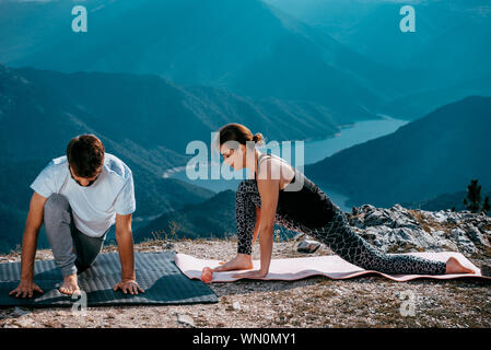 Fitness, sport, and lifestyle concept - couple making yoga exercises on mountain - Stock Photo