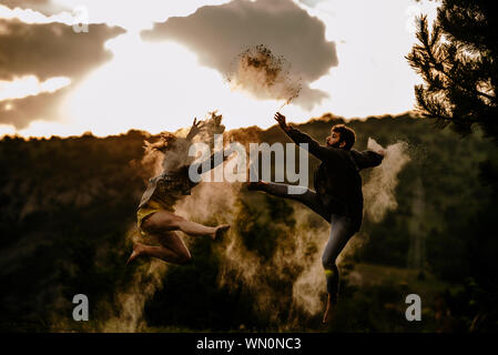 Handsome man with a beautiful young girl dancing while jumping on the mountain - Stock Photo