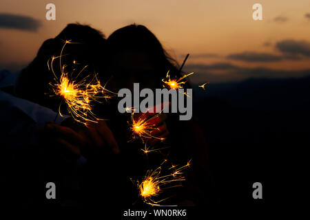 Portrait of young attractive celebrating couple holding firecrackers - Stock Photo