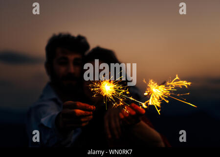 Silhouette woman and man holding a burning sparkler firework bengal light - Stock Photo