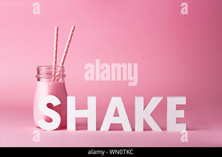 Raspberry Smoothie In Jar With Straws By Text Against Pink Background