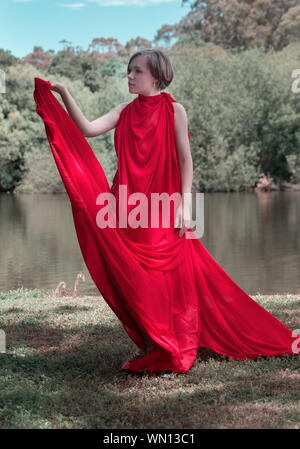 Woman Covered In Red Dress Standing At Lakeshore - Stock Photo