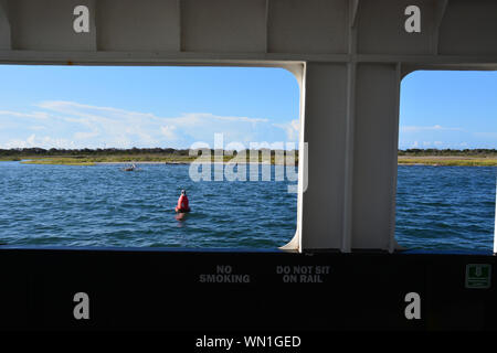 Hatteras Island passes by outside the window of the Hatteras-Ocracoke car ferry on the Outer Banks of North Carolina. - Stock Photo