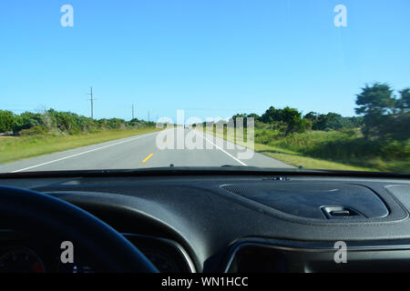 Looking out the front windshield of a car traveling down NC-12 on the Outer Banks of North Carolina. - Stock Photo