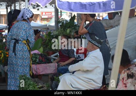 Vendors and customers in Siaab Bazaar, Samarkand, Uzbekistan - Stock Photo