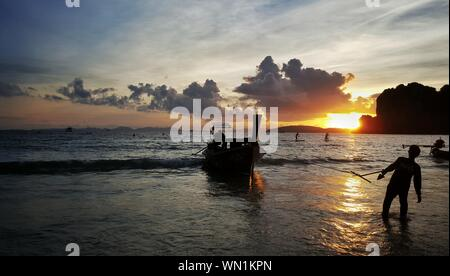 Silhouette Man Pulling Boat On Shore Against Sky During Sunset - Stock Photo