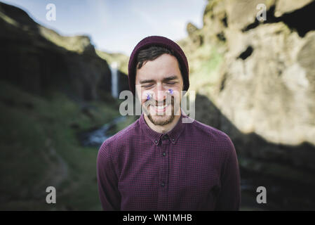 Smiling man with flowers on his face by Kvernufoss waterfall in Iceland - Stock Photo
