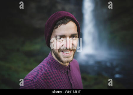 Portrait of smiling young man by Kvernufoss waterfall in Iceland - Stock Photo